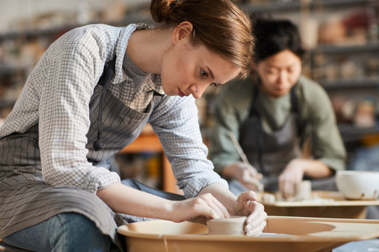 Serious concentrated young woman sitting at pottery wheel and adjusting edges of clay vessel while making pot in workshop