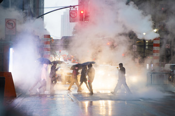 Undefined people with umbrellas are crossing the 42nd street in Manhattan. Steam coming out from...