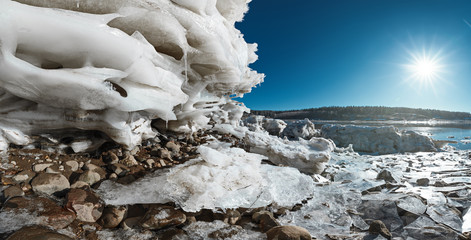 Panoramic view of lake at winter day, layers of ice and rocks on foreground, Moscow region, Russia