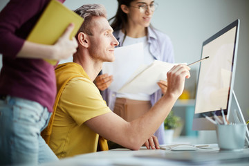 Side view portrait of contemporary business team using computer together, focus on man pointing at...