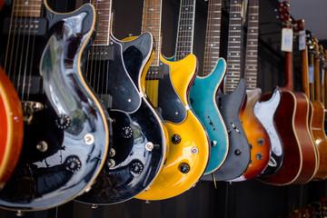 Spoed Foto op Canvas Muziekwinkel Electric guitars In a music instruments shop. Parts of guitar, guitar body