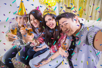 Happy young people take selfie at a birthday party