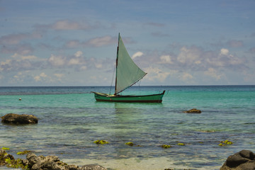 photo of a sailing boat in the sea with blue sky and white clouds