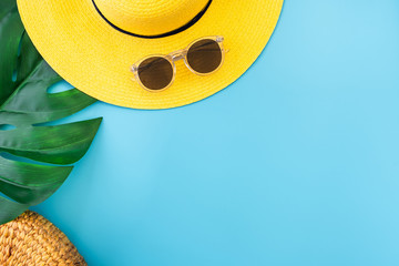 summer blue banner with yellow hat ,sunglasses and monstera leaf on blue background top view