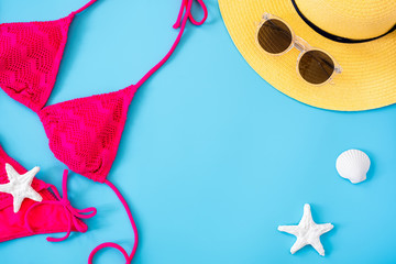Wall Mural - summer blue banner with yellow hat ,pink bikini,sunglasses and seashell on blue background top view.