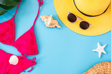 Wall Mural - summer blue banner with yellow hat ,sunglasses and pink bikini on blue background top view.
