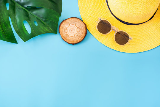 summer blue banner with yellow hat ,sunglasses and monstera leaf on blue background top view.