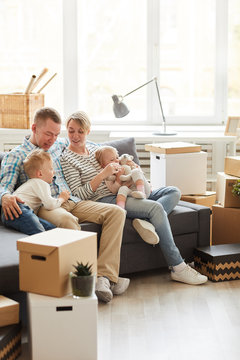 Content young family with two children sitting on sofa and planning repair after moving into new home, unpacked boxes stacking in living room