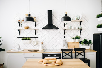 Spacious modern Scandinavian loft kitchen with white tiles and black appliances. Bright room. Modern interior. Baguettes on a plant in front.