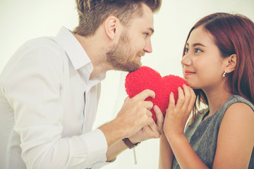 Couple lover in love holding red heart shape and looking in their eye. Couple Smiling fall in love.