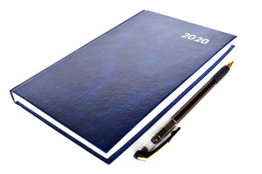 Closed blue leather notebook for new year with text 2020 on cover and office black ballpoint pen on white background. Isolated
