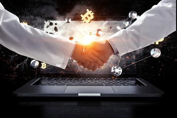 Business handshake by a man and a woman and a laptop. Mixed media