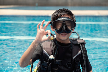 Young little Asian boy scuba diver showing ok hand signal, diving lessons for beginners