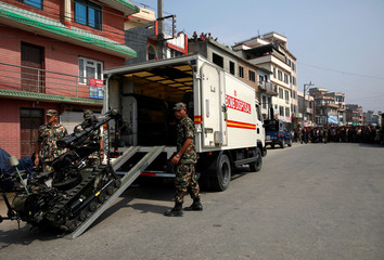 Members of bomb disposal team work to defuse an improvised explosive device upon their arrival in Lalitpur