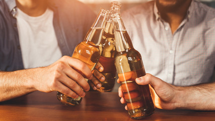 Mates Clinking Bottles Of Beer In Pub