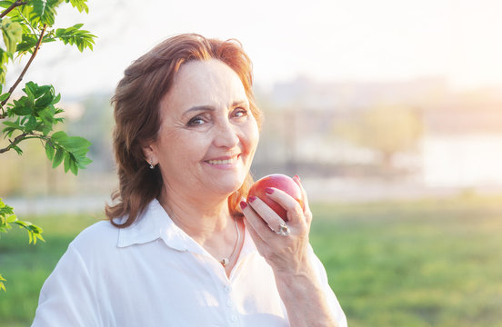 Beautiful happy smiling elderly woman holding a red apple in her hands, healthy diet concept