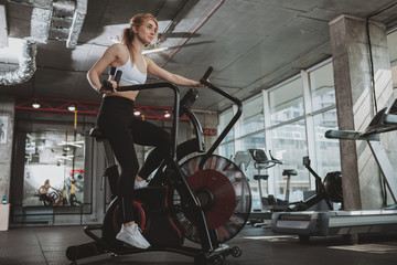 Healthy athletic woman doing intense workout on air bike at the gym, copy space. Fitness female with toned strong body cycling at sport studio, using air bicycle Fototapete