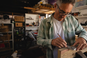 Carpenter using graduated square on wooden plank in workshop