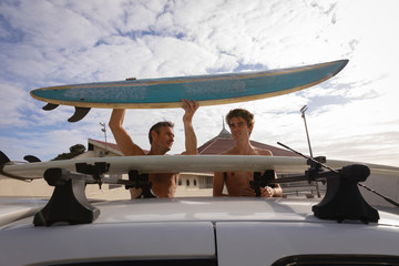 Father and son removing surfboard from car carrier