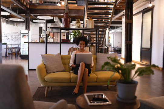 Happy businesswoman sitting on yellow sofa while she is using laptop