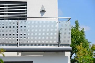 Moderner Balkon mit elektrischer Markise, Balkonlampe, Edelstahl-Geländer, Jalousien und in die Außenwand integriertes Regenfallrohr an einer Neubau-Hausfront