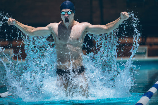 Young swimmer with arms stretched out celebrate victory in pool