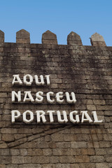 """Defensive stone wall with the sign: """"Here Portugal was born""""; in Guimaraes"""