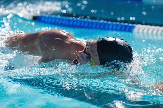 Male swimmer swimming freestyle in swimming pool