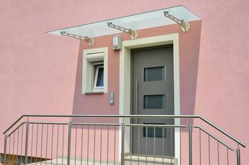 Fototapeta Moderner Hauseingangsbereich mit Glas-Vordach an einem neu gebauten Mehrfamilien-Wohnhaus mit Büros obraz