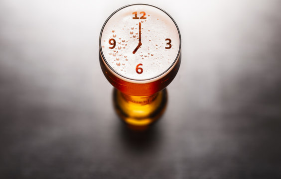 Time for beer concept. Clock or watch symbol on beer glass foam on black table, view from above