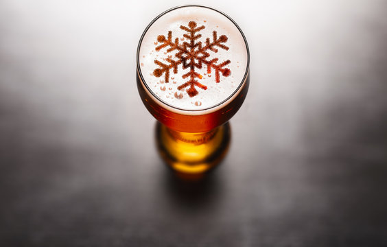 Christmas or New Year beer concept. Snow symbol on beer glass foam on black table, view from above