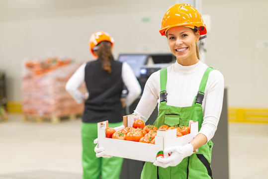 Healthy food production concept. Portrait of young smiling woman working in warehouse.