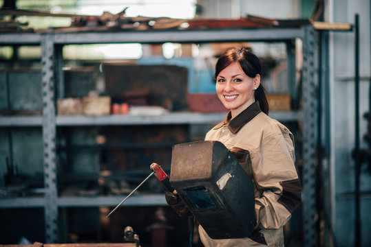 Portrait of a beautiful female welder at work, smiling at camera.