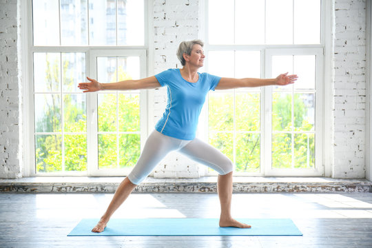 Sporty mature woman practicing yoga at home