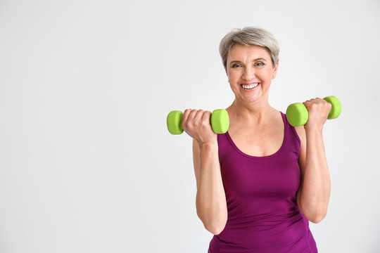 Sporty mature woman with dumbbells on light background