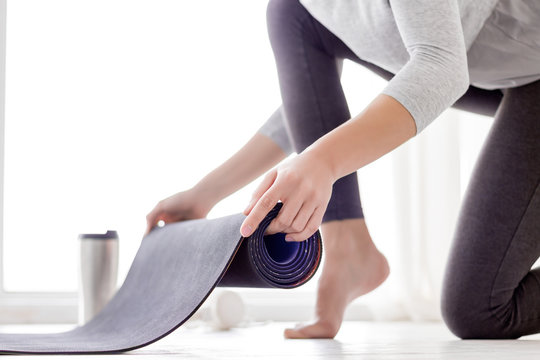 Closeup of beautiful female hands is holding rolling out sport mat. Young athletic woman in grey uniform clothes is preparing to practice yoga, have meditation, relax at light fitness studio.