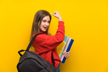 Teenager student girl over yellow background making strong gesture Wall mural
