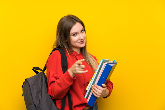 Teenager student girl over yellow background points finger at you