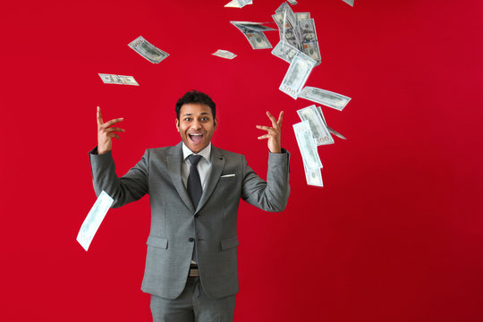 Happy businessman and falling dollar banknotes on color background