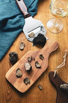 Black truffles slices in wooden board