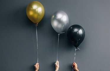 Close-up of black silver and gold balloons caught in hands