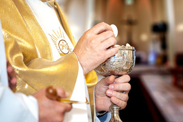Priest gives first communion.