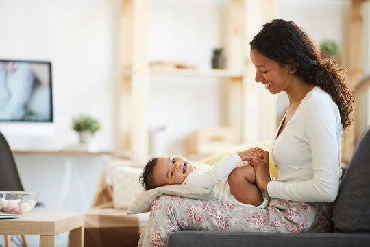 Positive beautiful young African mother with curly hair expressing her love relation to laughing baby son while playing with him