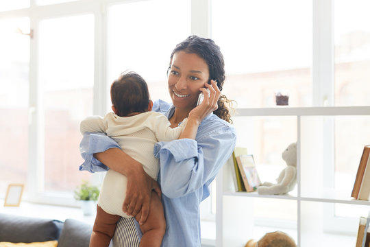 Smiling beautiful young black mother standing in living room and talking on cellphone while nursing baby