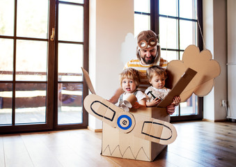 Wall Mural - A father and toddler chidlren playing with carton plane indoors at home.