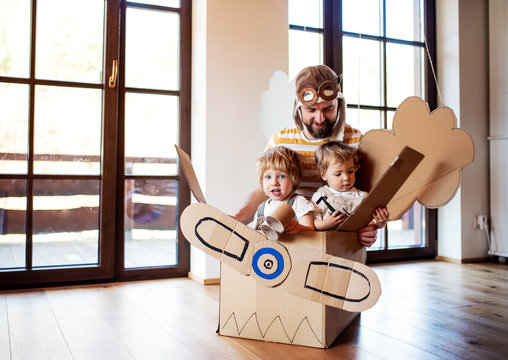 A father and toddler chidlren playing with carton plane indoors at home.