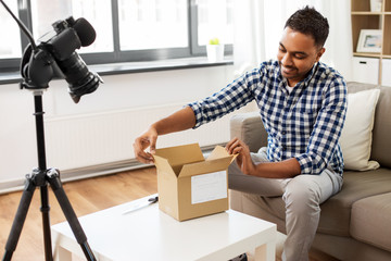 mail delivery, shipment and blogging concept - happy indian male blogger opening parcel box and recording video by camera at home