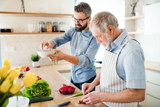 An adult hipster son and senior father indoors at home, cooking.