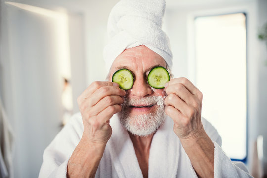 Senior man with cucumber on front of his eyes in bathroom indoors at home.