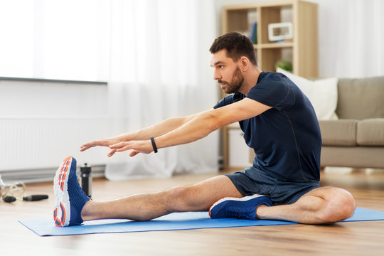 sport, fitness and healthy lifestyle concept - man stretching leg on exercise mat at home